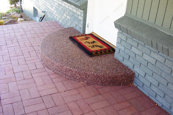 Exposed aggregate porch surrounded by brick pavers